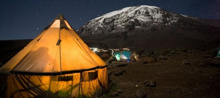 Africa Tanzania Kilimanjaro National Park MR Climbing parties tents glow against night sky at Karanga Camp